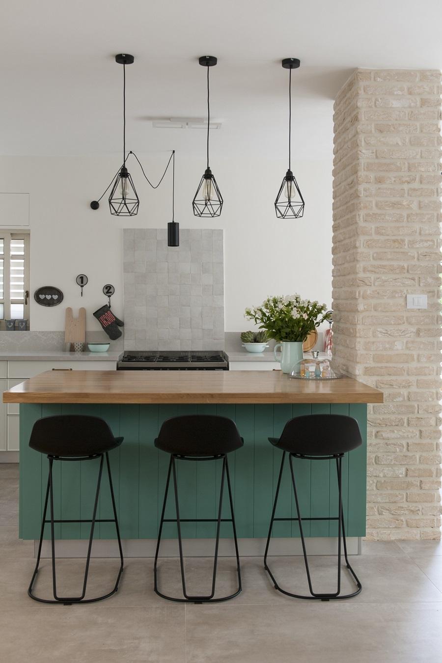 אי למטבח מעץ ירוק וכיסאות שחורים